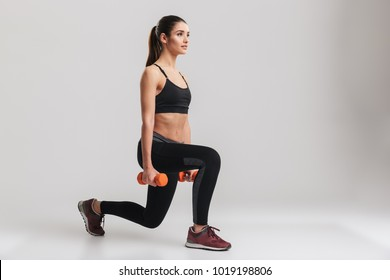 Photo of sporty caucasian woman squatting with small weights isolated over gray background