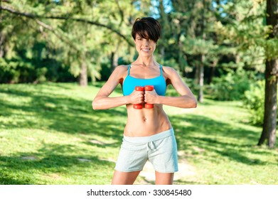 Photo of sporty slim girl outdoors at morning. Young beautiful woman smiling, looking at camera and doing sport exercises with dumbbells while training in park