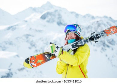 Photo of sporty woman with skis on her shoulder against background of snowy hill