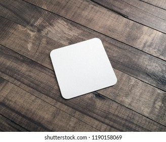 Photo of square beer coaster on wooden background. Blank template for your design.