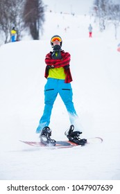 Photo of standing athlete with snowboard in winter park during day.
