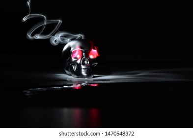Photo of a steel skull on black glass with a red and white flashlight