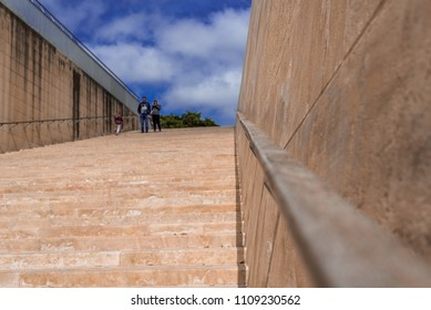 Photo of Stone stairs and wall with metal rail in the ancient center of Valletta, Malta. Blue, cloudy sky background