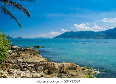 Photo of stones on coast near sea with mountains in distance in Florianopolis in Brasil.