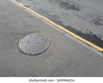 Photo of the street with part of the pavement and the roadway; on the sidewalk there is a manhole, on the roadway there is a yellow strip.