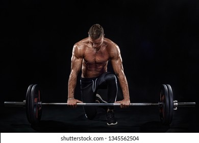 Photo of strong muscular bodybuilder athletic man pumping up muscles with barbell on black background. Workout energy bodybuilding concept.