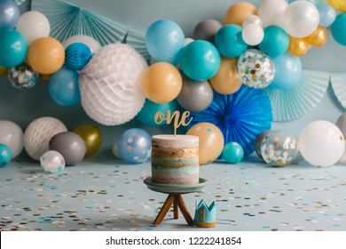 Photo Studio of One Birthday Party or firts birthday cake with Blue and white Ballons with colorful confetti . Cake smash. One year. Ballons garlands