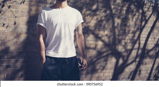Photo style man with tattoo wearing blank white tshirt. Stands in front of a brick wall. City street background. Horizontal mockup.