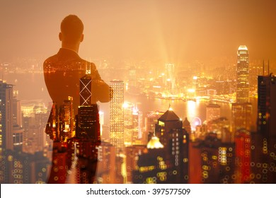 Photo of stylish adult businessman wearing trendy suit and looking night city. Double exposure, panoramic view contemporary City background. Horizontal, bokeh, blurred