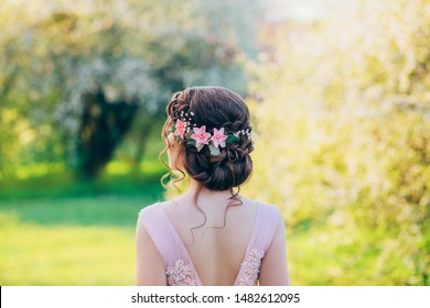 Photo of a stylish evening hairstyle for long hair, which are collected in an elegant bun with delicate, airy, curly locks. Wreath decoration with pink flowers and beads. Rear view