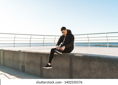 Photo of stylish guy 20s in black tracksuit tying his shoelaces while running by seaside along pier during morning workout