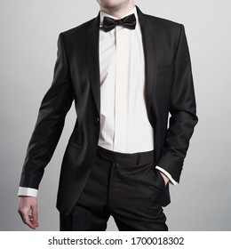 Photo of stylish man in elegant black suit with tie. Fashionable young model pose in photography studio. Luxury evening smoking with white shirt.