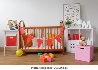 Photo of stylish room for babygirl with wooden crib