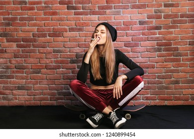 Photo of subcultural sporty girl 20s sitting on skateboard with cigarette against brick wall