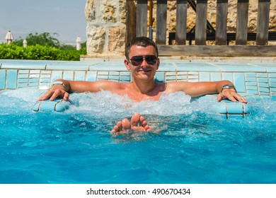 Photo of the Successful man relaxing in pool jacuzzi outdoor at spa resort enjoying luxury life. Success, healthy lifestyle, body care concept.