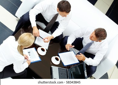 Photo of successful partners discussing business plan at meeting