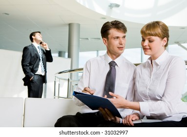 Photo of successful partners planning work with calling man at background