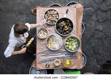 Photo of Summer grilling food. Up view of a man stringing vegetables on skewer
