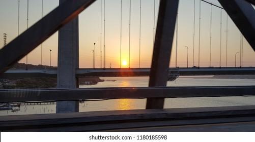 A photo of the sun setting on the water through the girders of a San Francisco area bridge