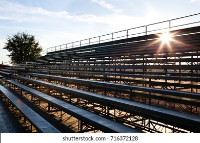 A photo of sunlight coming through empty bleachers with a tree and and a blue sky with clouds in the the background.
