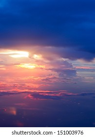 a photo of sunset above clouds from airplane window