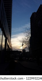 photo of sunset between buildings,  road traffic and atumn tree