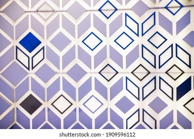Photo of the surface of a luminous wall with three-dimensional shapes of triangles, lines and squares. Abstract design background.