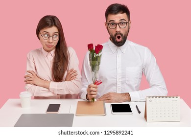 Photo of surprised bearded young man in elegant white shirt, holds red roses, looks through spectacles, has romantic relationships with colleague, sit together at coworking space. Perfectionism