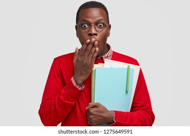 Photo of surprised black man covers mouth with palm, has scared expression, carries textbooks, dressed in red jumper and spectacles, stands against white background, afraids of shocking rumour