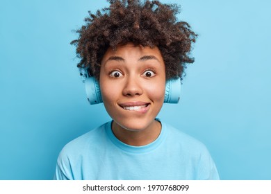 Photo of surprised curious Afro American woman bites lips looks directly at camera wears wireless headphones dressed in casual t shirt isolated over blue background. People leisure lifestyle