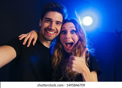 Photo of a surprised emotional happy young amazing loving couple having fun resting in a night disco club on concert showing thumbs up gesture.