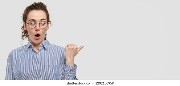 Photo of surprised emotive freckled female with curly dark hair, has amazed expression, dressed in fashionable clothes, points with thumb aside, shows free space for your advertising content