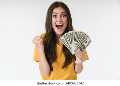 Photo of a surprised excited young girl isolated over white wall background holding money make winner gesture.