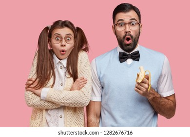 Photo of surprised female and male wonks stare with disbelief, eat delicious banana, dressed in old fashionable clothes, being puzzled by terrible news, isolated over pink background. Reaction concept
