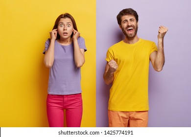 Photo of surprised female plugs ears, shocked with noise, glad man clenches fists, celebrates triumph, yells loudly from happiness. Boyfriend and girlfriend stand over purple and yellow wall