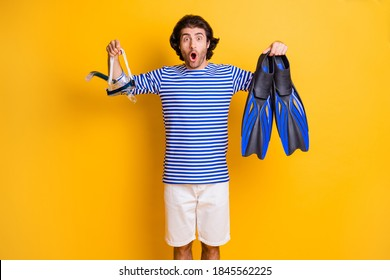 Photo of surprised guy hold scuba diving fins breathing mask goggles wear blue white shorts isolated on yellow color background