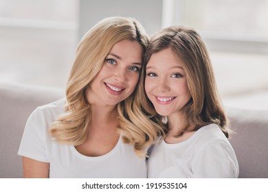 Photo of sweet charming mommy daughter wear white t-shirts smiling hugging sitting couch inside indoors home room