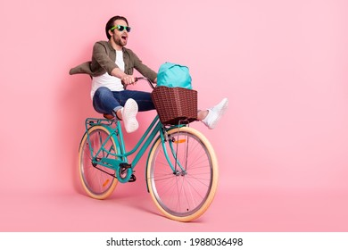 Photo of sweet cute guy dressed brown shirt dark eyeglasses riding bike backpack looking empty space isolated pink color background