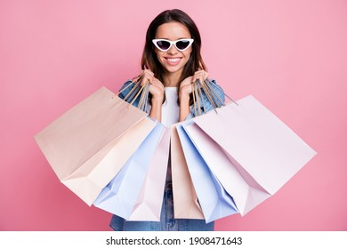 Photo of sweet excited wavy young woman wear denim outfit dark glasses holding many shopping bags isolated pink color background