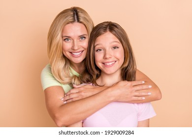 Photo of sweet happy attractive mother and daughter hug from behind family isolated on beige color background
