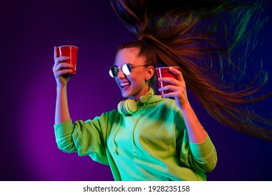 Photo of sweet shiny young lady wear green sweater holding two red paper glasses dancing isolated colored bright shine background