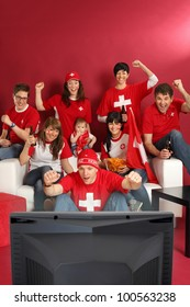 Photo of Swiss sports fans watching television and cheering for their team. Plenty of copyspace.