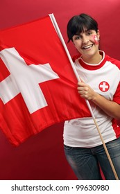 Photo of a Swiss sports fans waving a flag and cheering for her team.