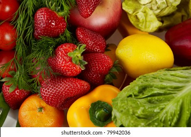 Photo of a table top full of fresh vegetables, fruit, and other healthy foods