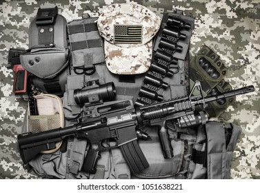 Photo of a tactical vest, rifle, gun, hat with american flag badge and cartrige belt laying on camouflage background.