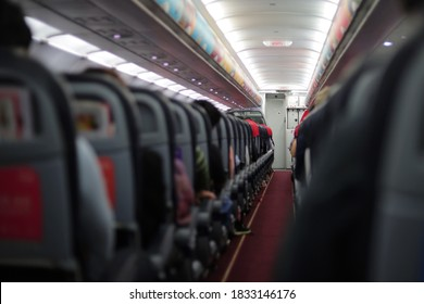 A photo take in airplane with traveler when take off are including the door access to Cockpit room (Airplane control room) and seats. Traveler sitting on the seat.