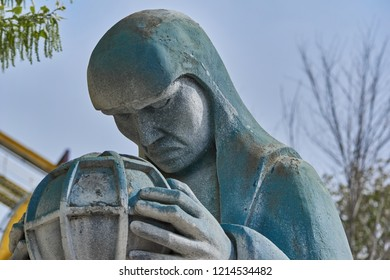 Photo taken close up in the foreground of the thoughtful Gotham stone statue in San Martin de la Vega, Madrid, Spain