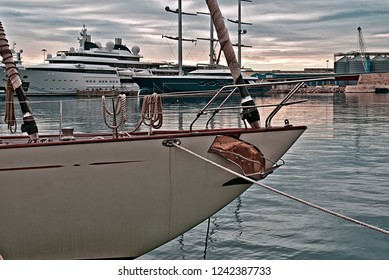 photo taken on 11-25-18 in Tarragona (Spain). Port of Tarragona, in the forefront the prow of a sailboat and in the background two yachts of Arab sheikhs
