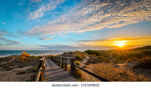 Photo taken in Punta Umbria, Huelva, Spain. It is a plank path that leads to the beach, in a magical sunset.