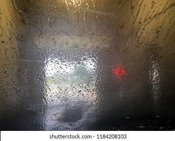 Photo taken of soap and water on window looking out the open door of a carwash.